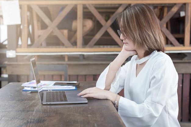 Geschäftsfrau, die durch den computer oder laptop arbeiten im bürocafé verwendet.