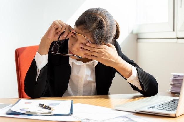 Geschäftsfrau, die durch schließen des auges beim arbeiten im büro stillsteht.