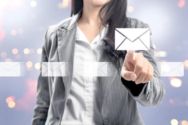 Geschäftsfrau, die e-mail-ikonen auf virtuellem schirm zeigt