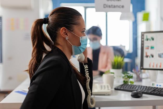 Geschäftsfrau, die ein gespräch über das festnetz führt und die soziale distanzierung mit mitarbeitern aufrechterhält, die aus kunststoff mit gesichtsmaske bedeckt sind, um eine infektion während der globalen pandemie von covid19 zu verhindern.