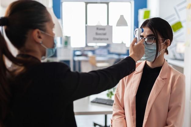 Geschäftsfrau, die ein infrarot-thermometer auf die stirn eines kollegen setzt