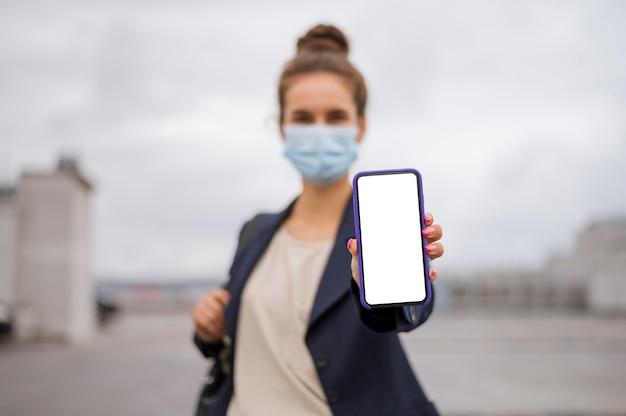 Geschäftsfrau, die ein leeres smartphone hält, während sie eine medizinische maske trägt