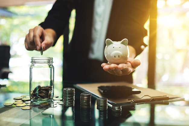Geschäftsfrau, die ein sparschwein hält, während münze in ein glas steckt, um energie- und geldkonzept zu sparen