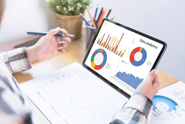 Geschäftsfrau, die ein tablet verwendet, um das erfolgskonzept der finanzstrategiestatistik des unternehmens zu analysieren und die zukunft im büroraum zu planen.