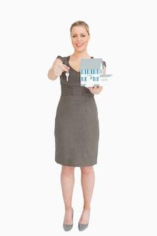 Geschäftsfrau, die ein vorbildliches haus und einen schlüssel zeigt