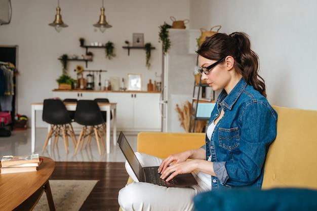 Geschäftsfrau, die eine e-mail auf laptop zu hause büro schreibt