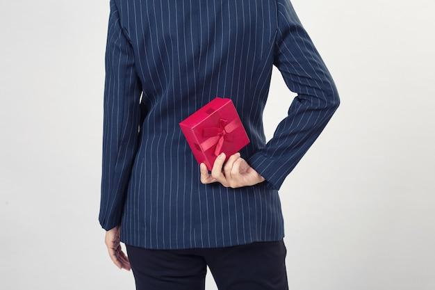 Geschäftsfrau, die eine geschenkbox hinter ihrem rücken hält