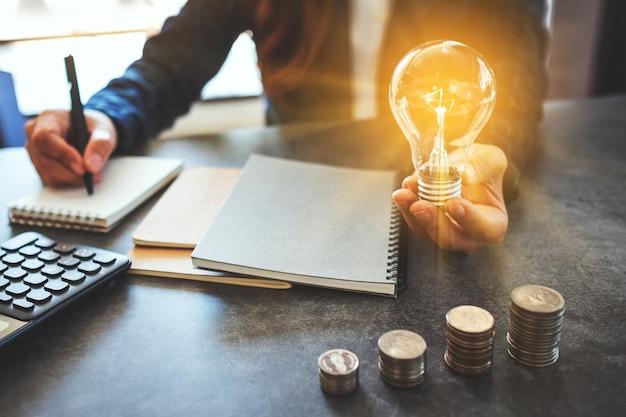 Geschäftsfrau, die eine glühbirne hält, während sie notizbuch mit münzstapel auf dem tisch notiert, energie- und geldkonzept spart