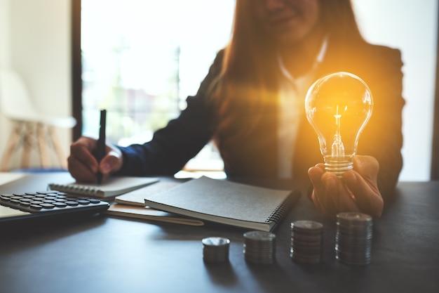Geschäftsfrau, die eine glühbirne mit münzstapel auf dem tisch hält, energie- und geldkonzept spart