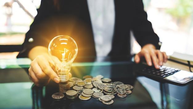 Geschäftsfrau, die eine glühbirne über münzenstapel auf den tisch legt, während für das energiespar- und geldkonzept berechnet wird