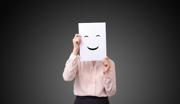 Geschäftsfrau, die eine karte mit dem zeichnen von gesichtsausdruckillustrationsgefühl-gefühlsgesicht auf weißbuch hält