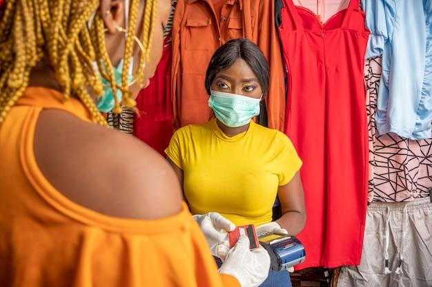 Geschäftsfrau, die eine kreditkarte von einem kunden abholt, gesichtsmaske und handschuhe trägt