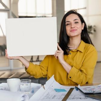 Geschäftsfrau, die eine leere karte bei der arbeit hält