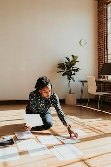 Geschäftsfrau, die eine marketingstrategie auf einem holzboden plant