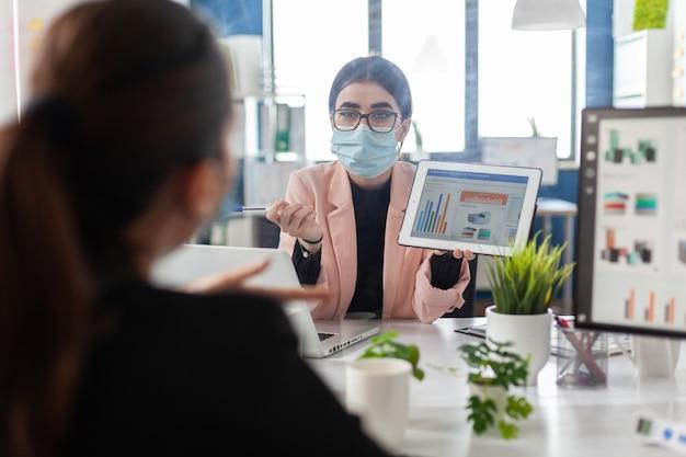 Geschäftsfrau, die eine medizinische gesichtsmaske gegen covid trägt und ein finanzdiagramm zeigt
