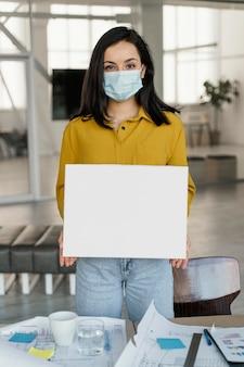 Geschäftsfrau, die eine medizinische maske trägt, während sie eine leere karte hält