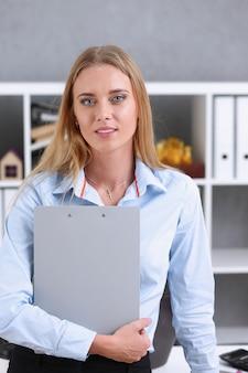 Geschäftsfrau, die eine schreibtafel im büro hält