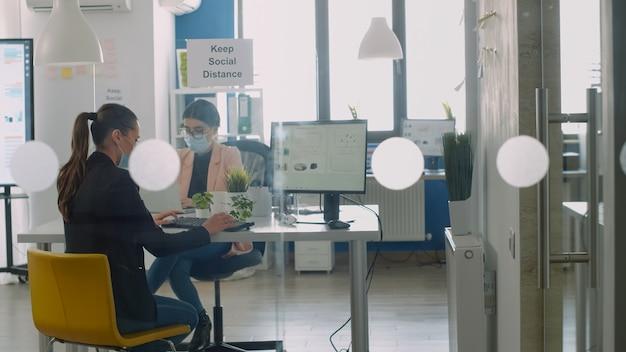 Geschäftsfrau, die eine schützende gesichtsmaske trägt, die am computer arbeitet und mit kollegen über geschäftsjobs diskutiert. mitarbeiter halten soziale distanz ein, um viruserkrankungen während der globalen epidemie zu vermeiden