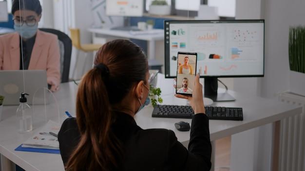 Geschäftsfrau, die eine schützende gesichtsmaske trägt, die das telefon für eine online-videoanrufkonferenz mit einem remote-team verwendet. kollegen, die im hintergrund arbeiten und die soziale distanz respektieren