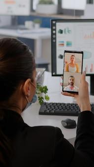 Geschäftsfrau, die eine schützende gesichtsmaske trägt und das telefon für eine online-videokonferenz nutzt