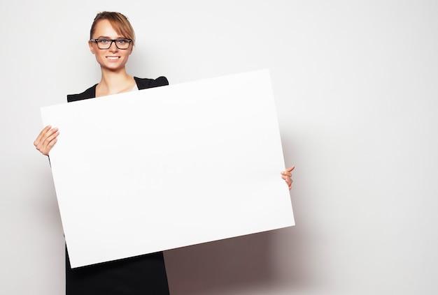Geschäftsfrau, die eine unbelegte anschlagtafel anhält.