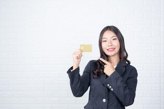 Geschäftsfrau, die eine unterschiedliche geldautomatenkarte, weiße backsteinmauer hält machte gesten mit gebärdensprache.