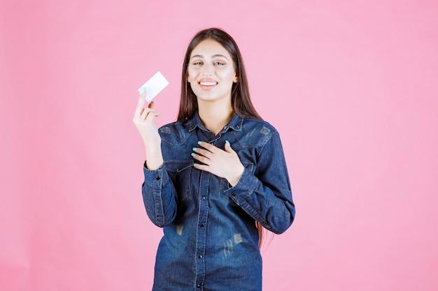 Geschäftsfrau, die eine visitenkarte hält und auf sich selbst zeigt