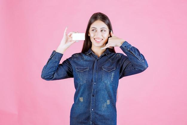 Geschäftsfrau, die eine visitenkarte hält und bittet, anzurufen