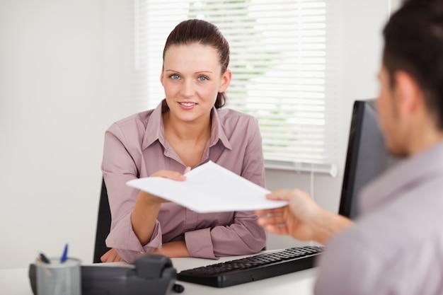 Geschäftsfrau, die einem kunden einen vertrag gibt