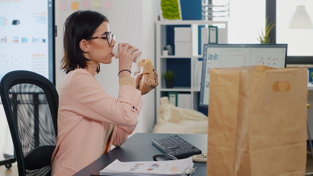 Geschäftsfrau, die einen bissen eines leckeren sandwiches isst und kaffee vor dem monitor trinkt