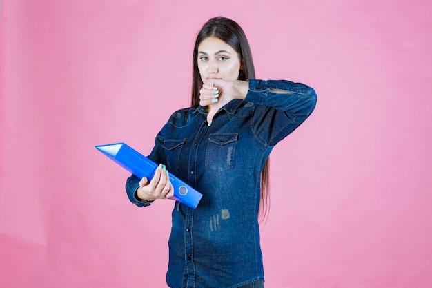Geschäftsfrau, die einen blauen ordner hält und daumen nach unten zeigt