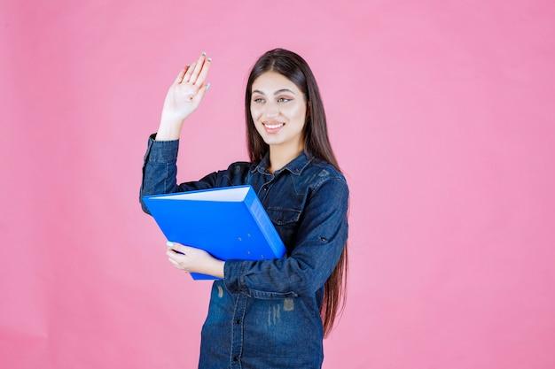 Geschäftsfrau, die einen blauen ordner hält und jemanden durch händeschütteln begrüßt