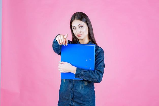 Geschäftsfrau, die einen blauen ordner hält und sie zeigt