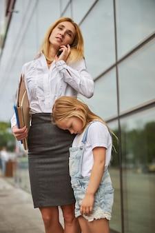 Geschäftsfrau, die einen ordner mit dokumenten in der hand hält und mit dem handy spricht, während sich ihre tochter nach einem langen tag langweilt