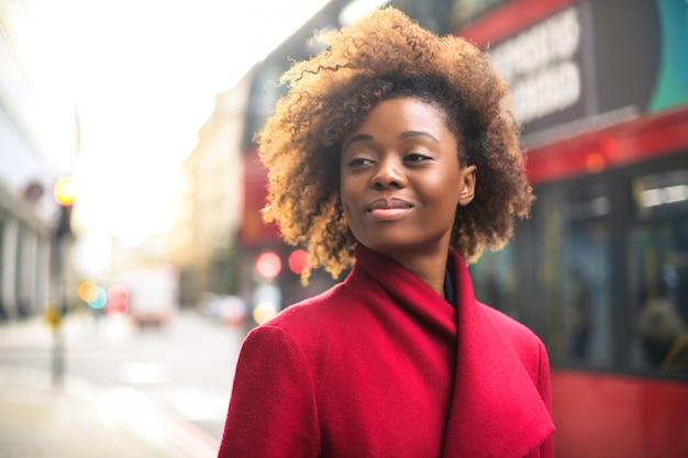 Geschäftsfrau, die einen roten mantel, gehend in die straße trägt
