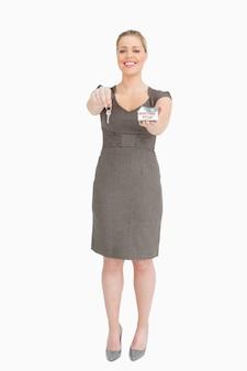 Geschäftsfrau, die einen schlüssel und ein musterhaus zeigt
