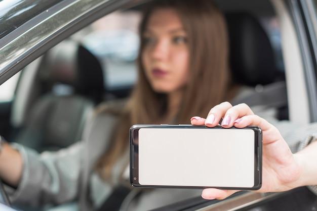 Geschäftsfrau, die einen smartphone im auto zeigt