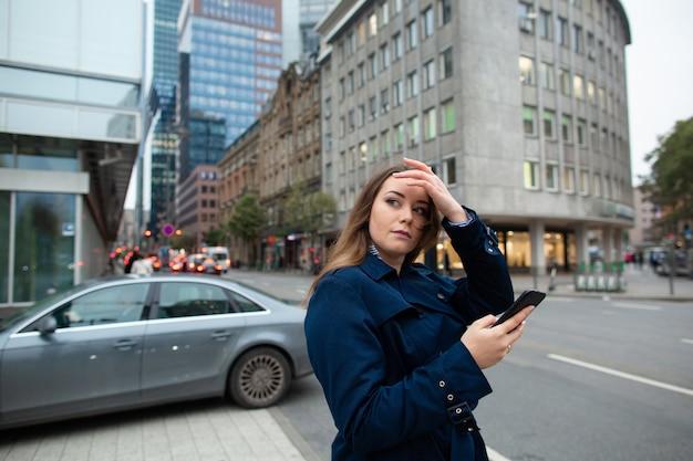 Geschäftsfrau, die einen standort im telefon, nach einem geschäftstreffen sucht. foto in halber länge.