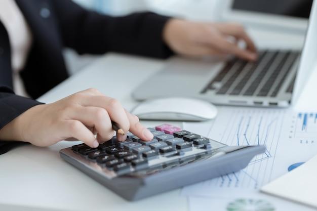 Geschäftsfrau, die einen taschenrechner verwendet, um die zahlen auf seinem schreibtisch in einem büro zu berechnen.