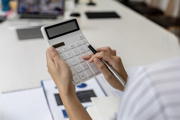 Geschäftsfrau, die einen taschenrechner verwendet, um zahlen in den finanzdokumenten eines unternehmens zu berechnen, analysiert sie historische finanzdaten, um das wachstum des unternehmens zu planen. finanzielles konzept.
