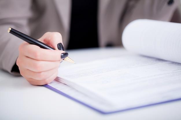 Geschäftsfrau, die einen vertrag über unterzeichnungszeile unterzeichnet