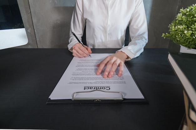 Geschäftsfrau, die einen vertrag unterschreibt
