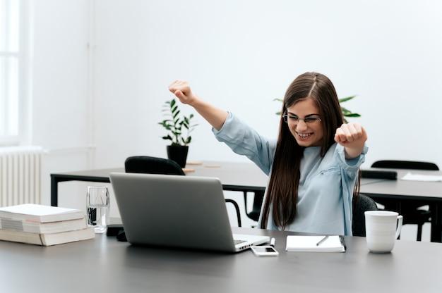 Geschäftsfrau, die erfolg im büro feiert.