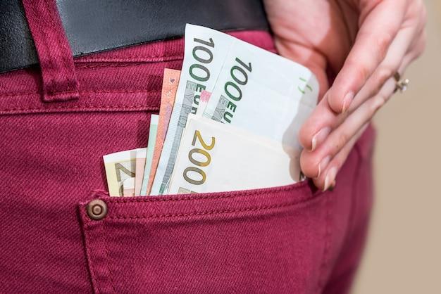 Geschäftsfrau, die euro-geldbanknoten in die tasche steckt