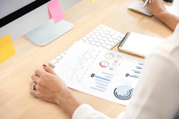 Geschäftsfrau, die finanzdiagramm im büro liest