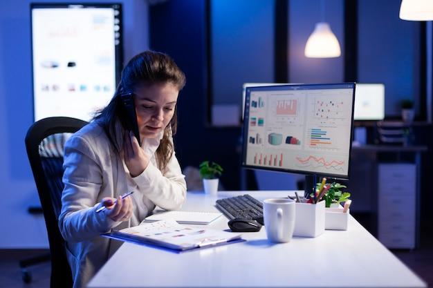Geschäftsfrau, die finanzdiagramme überprüft, während sie spät nachts im firmenbüro mit ihrem team auf dem smartphone spricht