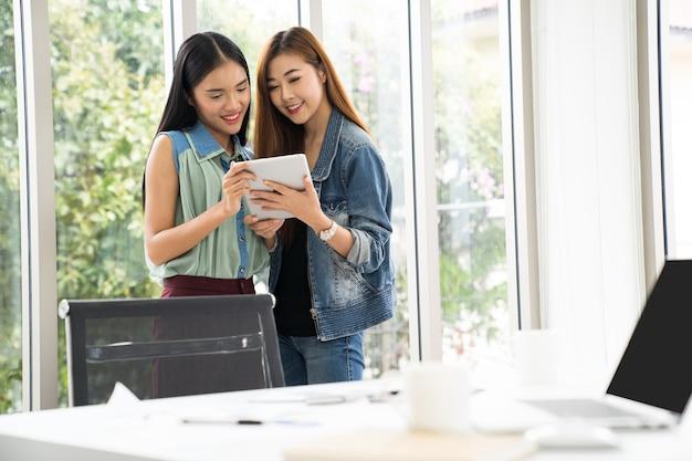 Geschäftsfrau, die finanzzahlen auf einer digitalen tablette bearbeitet und analysiert