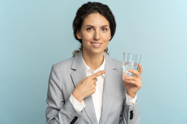 Geschäftsfrau, die finger auf wasserglas hält und zeigt, erinnert daran, nicht zu vergessen, wasser bei der arbeit zu trinken