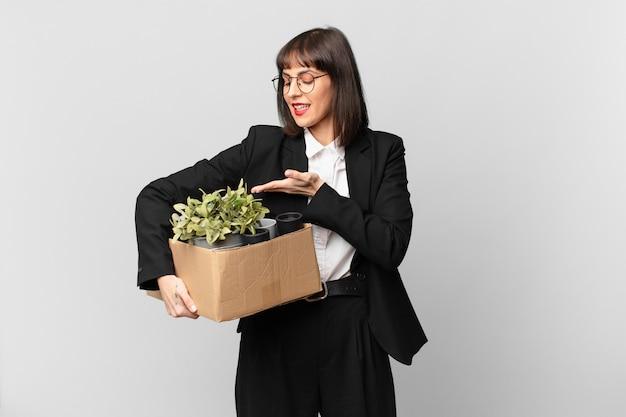 Geschäftsfrau, die fröhlich lächelt, sich glücklich fühlt und ein konzept im kopierraum mit der handfläche zeigt