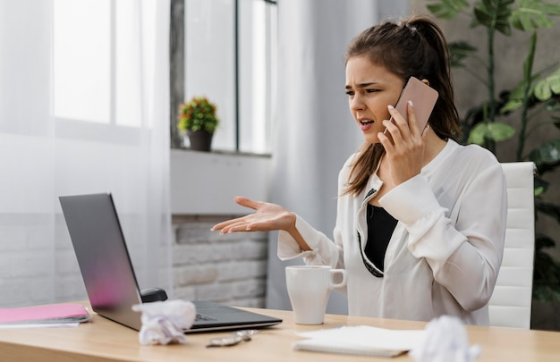 Geschäftsfrau, die frustriert schaut, während sie einen anruf hat
